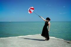 Red and White #4 (Mike Wood Photography) Tags: blue sky woman lake black color colour water sunshine standing umbrella concrete eos pier lakeerie dress teal arr allrightsreserved redandwhite umbrellacorp mikewood inthewind 400d aplusphoto mikewoodphotographycom mikewoodphotography misslizzz