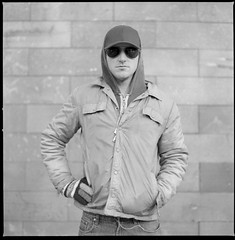 hood (s2art) Tags: portrait cold wall grey glasses blackwhite scan jacket hoody glove hood tmax400 2008 rescanned earbuds ngv reworked headon d25 nancyboy hasellblad headonsubmission