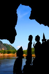Buda silhouettes  Laos (kees straver (will be back online soon friends)) Tags: travel blue sky orange sun mountain nature water statue clouds river temple coast boat asia southeastasia silhouettes monk buddhism delta cave laos buda mekong luangprabang pakoucaves mywinners abigfave anawesomeshot keesstraver