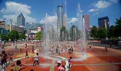 Fountain of Youth (RMac_Photography) Tags: city blue atlanta playing water sunshine skyline kids clouds ga buildings d50 georgia geotagged nikon cityscape action atl wideangle flags summertime 12mm fountains rmac betterthangood