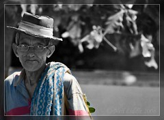 Old man walking down street with hat