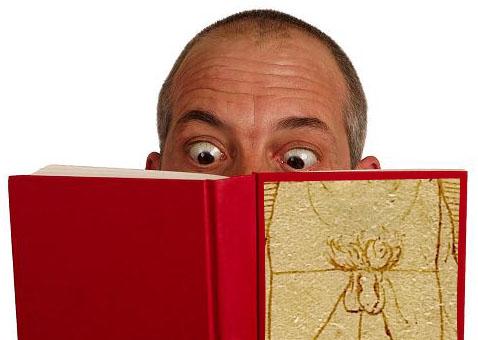 Fotografía de un hombre leyendo un libro rojo cuya portada es un plano del pene del Hombre de Vitruvio