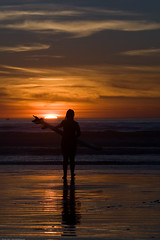Surfer Girl in Silhouette, standing with her surf board while totally mesmerized by the golden sunset - by mikebaird