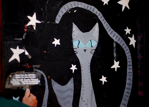 graffiti of a cat, tall and long, tail waved up over her head