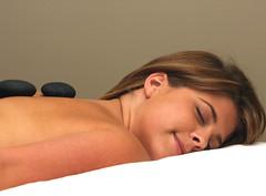 Kvinna masseras med varma stenar