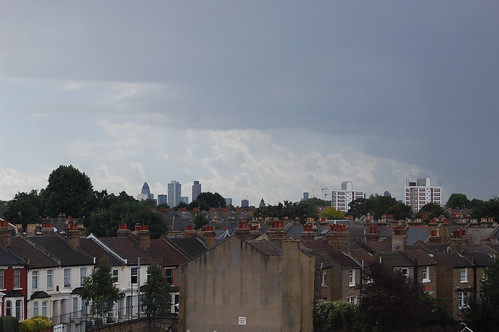 View over rows of rooftops and chimneys to the city of London skyscrapers beyond