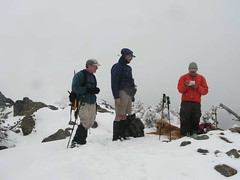 Snowing on the summit - David checking the summit register - How many days until summer?