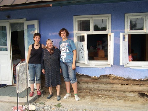 Valya and Olya with a woman outside of her damaged home