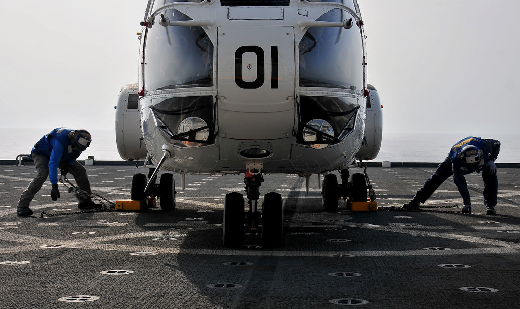 Civilian mariners remove tie-down chains and wheel chocks from a 330J Puma helicopter