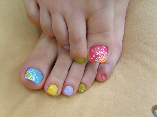 Flowers nail design for toe nails with pastel colors.
