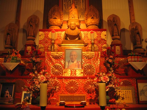 Buddha statue amidst candles and photos