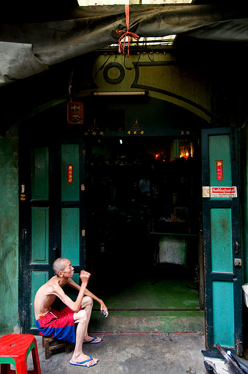 A resident of Bangkok's Chinatown in front of his home