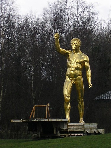 statue of golden man on a low loader