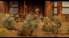 from THE ATTIC DOOR. Darrell (Actor Jake Johnson) hesitates before stepping into hot Western sun.