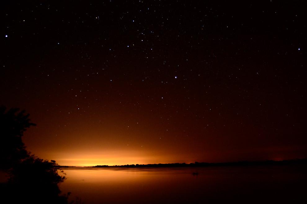 Otra toma panorámica con las luces de una ciudad al fondo y un bote de pescadores, avanzada la noche. (Rober Dam - Zanjita, Paraguay)