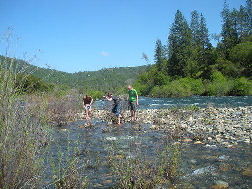 Boys at the river making a rock bridge