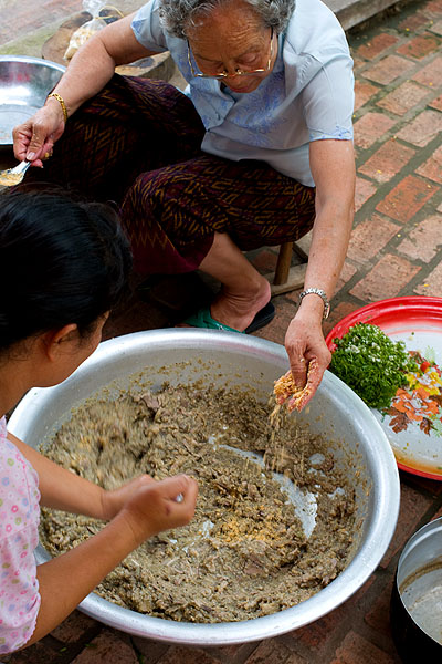 Two women making saem, a pork and eggplant 'salad' at a funeral in Luang Prabang