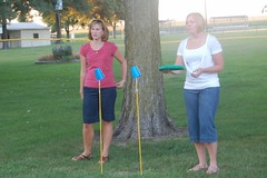 Brooke and Gwen play the cup-stick-frisbee game.