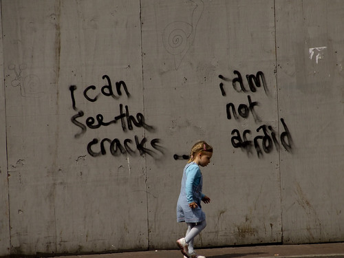 "girlchild skipping on the sidewalk -- behind her, on a wall, the graffiti reads, ""I can see the cracks -- I am not afraid."""