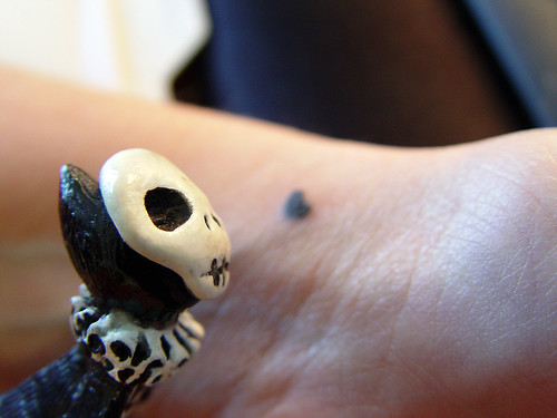 Skelly inspects a coworker's new tattoo