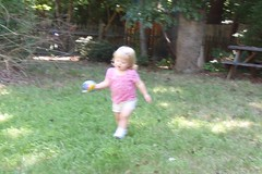 running with her ball across the yard