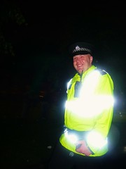 a laughing policeman !! (macgruff .. on / off !! V/Busy) Tags: portrait people man green smile night laughing scotland nightshot bright glasgow gig festivals parks police reflect nighttime jacket laugh copper vest radiohead policeman walkietalkie glasgowgreen hiviz radioheadgig laughingpoliceman checkerhat illuminatedvest hivizvest