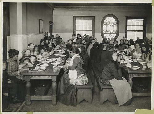Uncle Sam, host. Immigrants being served a free meal at Elli...