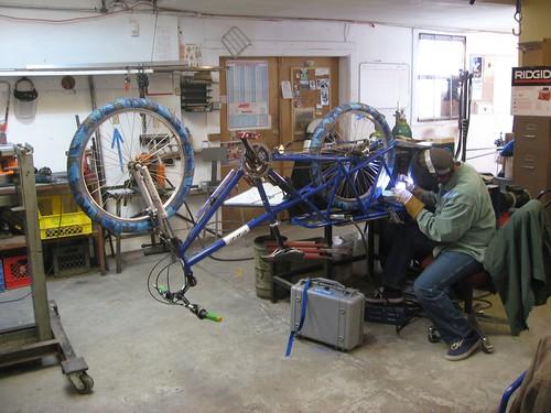 Gian welding a custom tab on a Mundo frame for faster loading of equippment.