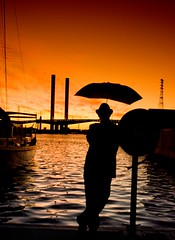 Tobacco Man Sunset (Vermin Inc) Tags: blue sunset portrait selfportrait man water silhouette umbrella pose person evening boat ship pentax australia melbourne victoria hose human filter docklands mast firehose charliechaplin boltebridge cokin umbrellaman tobaccofilter orangetones k10d umbrellawelfareagent sigma1224mmf35