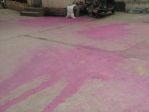 pink stains in driveway of apt building after Holi 230308