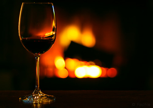 Copo de vinho com lareira ao fundo