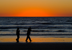 Couple walk in silhouette on Morro Strand State Beach