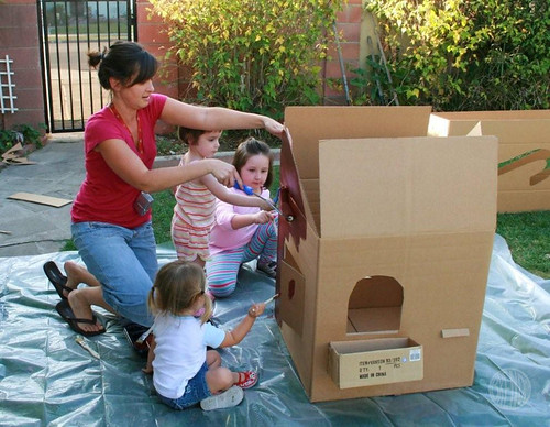 Women and kids painting life size cardboard gingerbread house