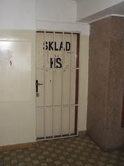 A door in the hallway, blocked with iron bars, some writing in Czech on it.