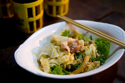 A dish of kuaytiaw khua kai, wide rice noodles fried with egg and chicken, as served on Charoen Krung Soi 16