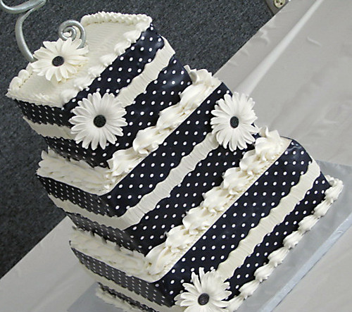 Three tiered square wedding cake decorated with edible images and black and