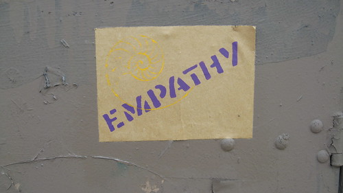 a wheat-pasted poster with the word EMPATHY in purple bold lettering. A yellow outline of a nautalus shell is just over the beginning of the word.