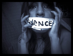 a woman with tape over her mouth, the word silence is written in capital letters on the tape