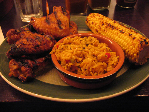 Chicken wings with Peri Peri sauce, spicy rice and corn on the cob