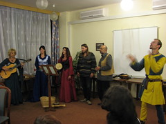 Five people in traditional garments singing folk songs, and another person juggling beside them