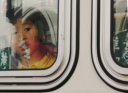 Child looking out of bus at city reflections