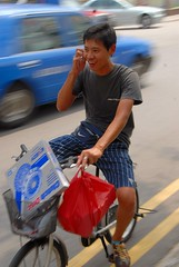 Mobile phoning (jeremyhughes) Tags: street red man motion blur smile smiling bike bicycle mobile movement nikon singapore cyclist phone basket stripes telephone cargo communication riding plasticbag mobilephone commuter commuting conversation shorts d200 littleindia nikkor panning rider striped dialogue telephoning phoning nikond200 stripyshorts
