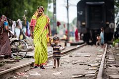 Indian woman walking with young boy (damonlynch) Tags: girls people india boys train children women delhi indian railwaystation newdelhi newdelhirailwaystation