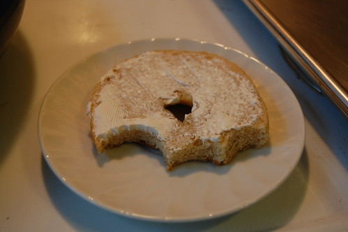 Half of a plain bagel with cream cheese, half eaten