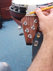 It was time to adjust the depth of the five notches in the nut.  One string at a time we strummed the string and tapped the string against the zero fret.