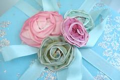 Ribbon Roses (such pretty things) Tags: christmas pink roses silver wrapping aqua pastel balls stamens bow ribbon giftwrap shabbychic mercuryglass seambinding millineryflowers