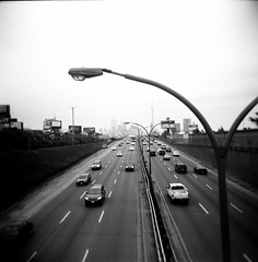 Holga from Above. (avp17) Tags: bridge light urban blackandwhite bw toronto ontario canada cars 120 film skyline square holga highway king day fuji cntower cne 120film diana dufferin dvp princessgates