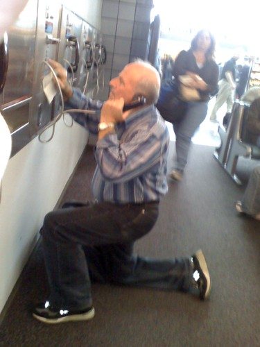 Guy struggling with pay phone @ ORD