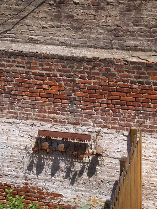 hanging metal scene on a brick wall