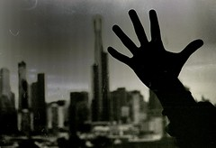 melbourne skyline meets the hand of dan (mugley) Tags: blackandwhite bw film dan window silhouette skyline 35mm buildings nikon shadows dof skyscrapers zoom bokeh towers grain australia victoria marks epson 135 dust nikkor polarizer eureka eurekatower stkildard f90x hairs urbanlandscape southmelbourne handmodel polariser v700 macophot 2870mmf3545 handportrait macocube400c mingmong